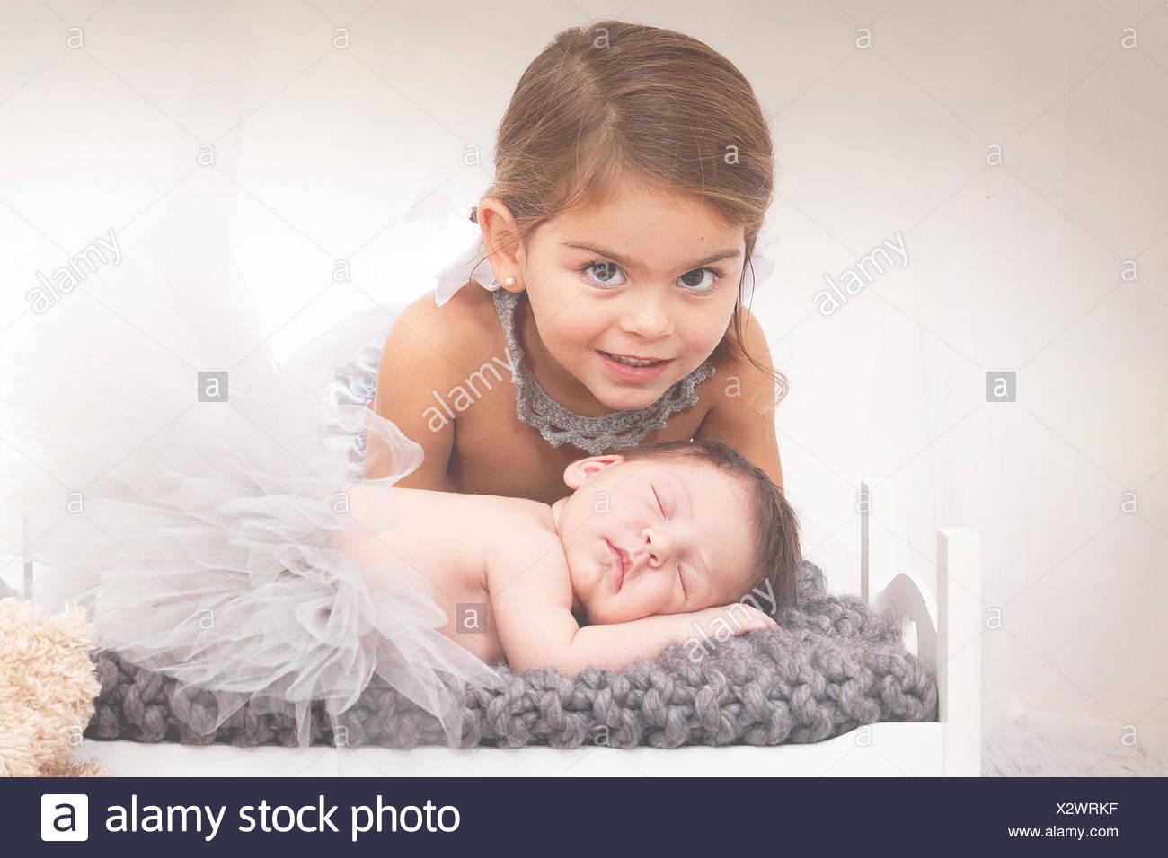Retrato de una niña con bebé recién nacido hermana Foto de stock
