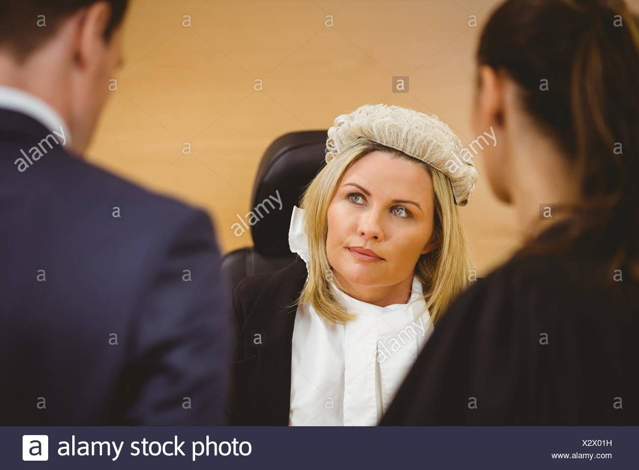 Juez y Abogado escuchando el criminal en esposas Foto de stock