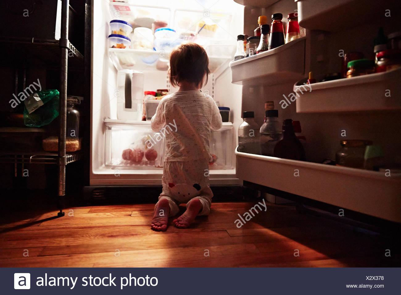 Vista trasera del niño varón arrodillado delante de la nevera abierta durante la noche Imagen De Stock