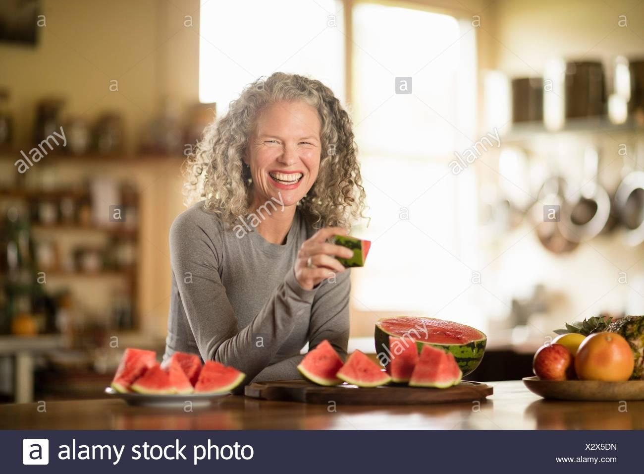 Retrato de mujer madura comiendo sandía en la cocina Foto de stock