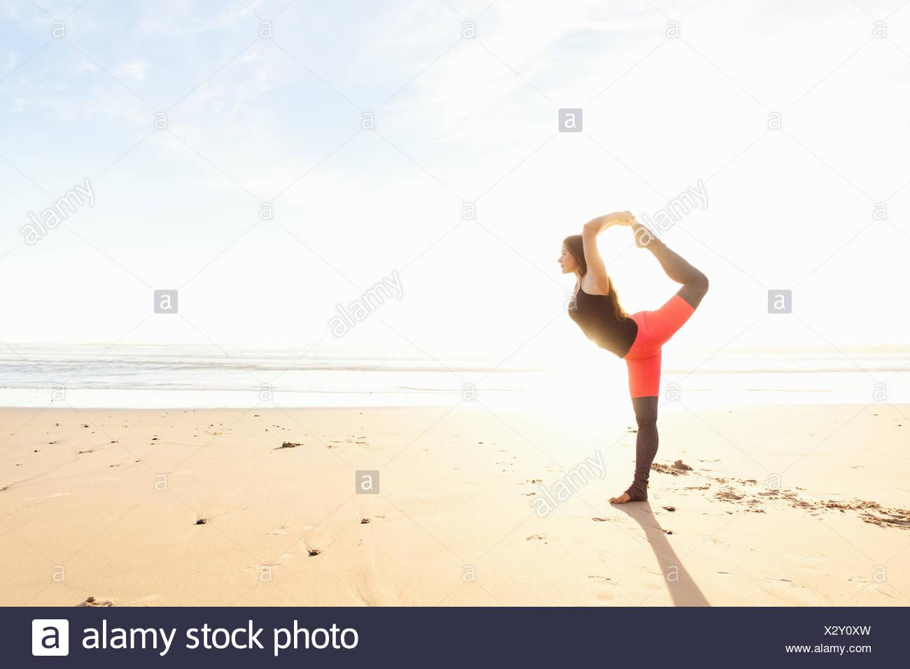 Mujer en pose de yoga en la playa Imagen De Stock