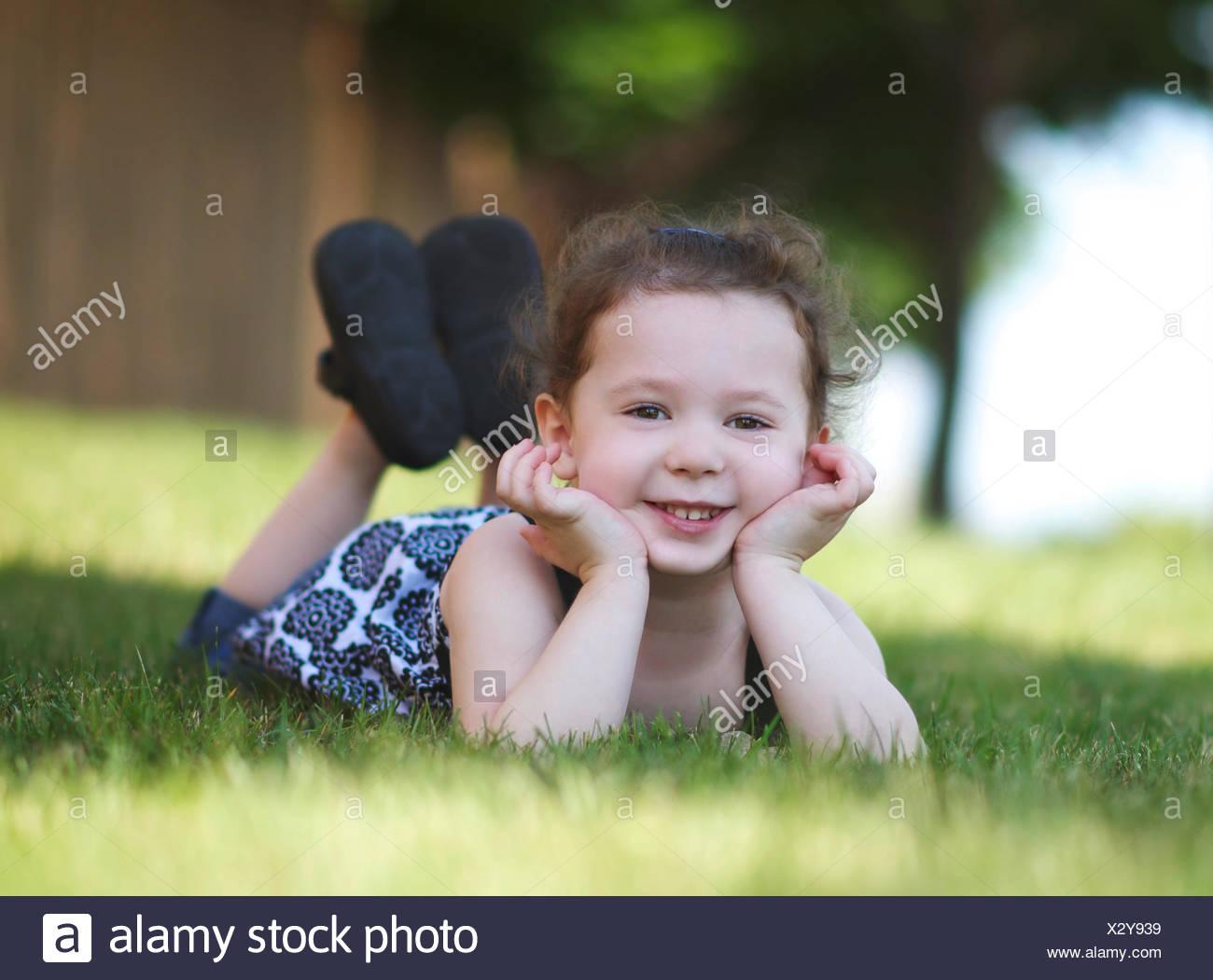 Niña alegre (4-5) posando sobre el césped Imagen De Stock
