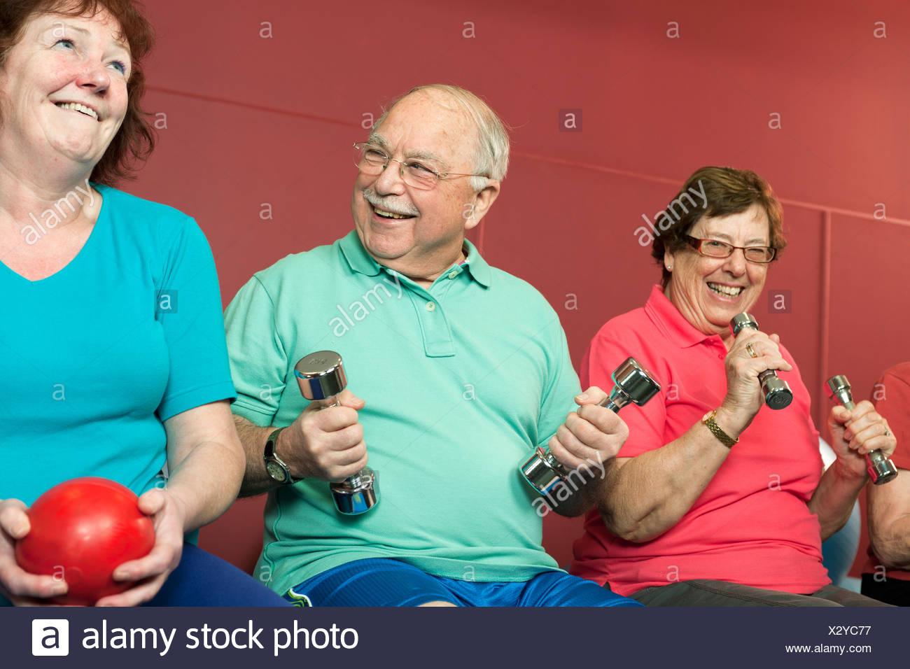 Las personas de edad, el levantamiento de pesas en el gimnasio Foto de stock