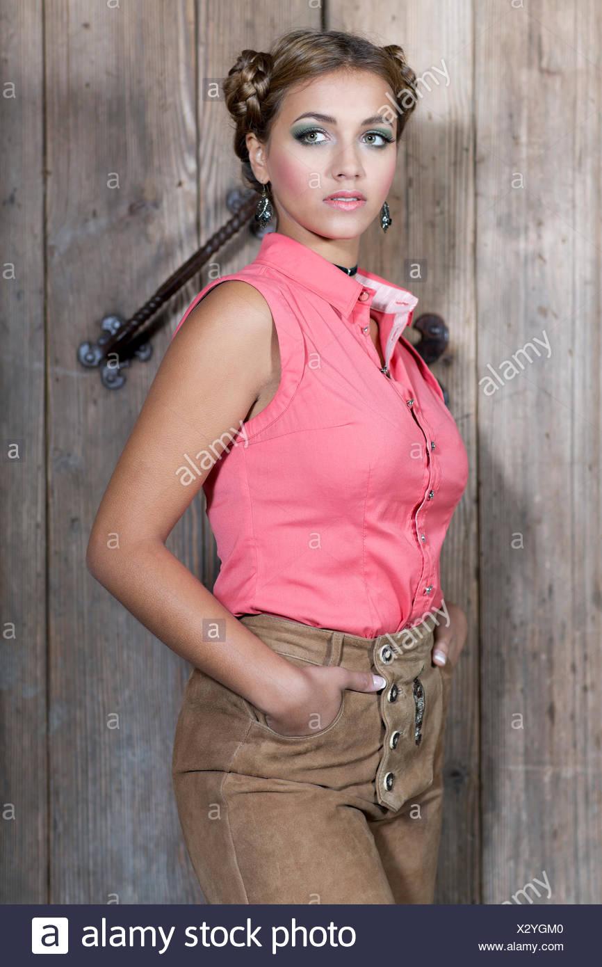 Mujer joven llevaba una rosa sin mangas y pantalones de cuero tradicional, dirndl buscar Imagen De Stock