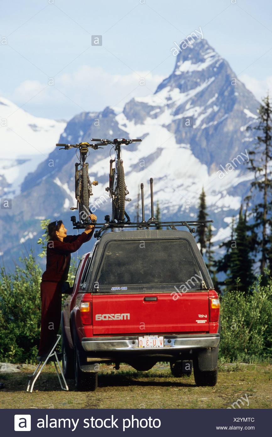 Una joven mujer teniendo una bicicleta de montaña de la roofrack de un camión, justo antes de aventurarse en la cuenca Keystone-Standard trail, Imagen De Stock
