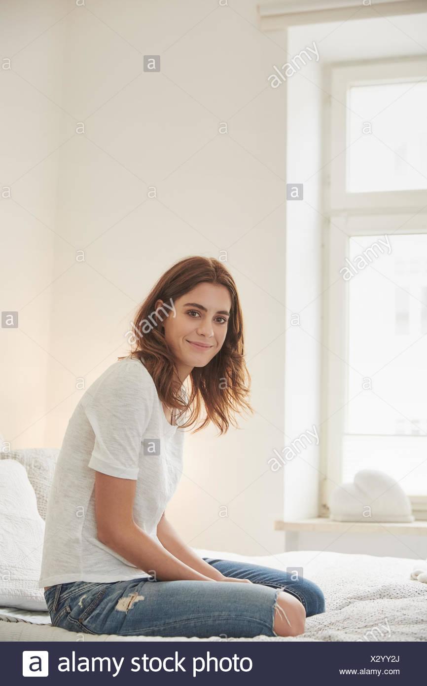 Retrato de mujer joven arrodillado en la cama Imagen De Stock