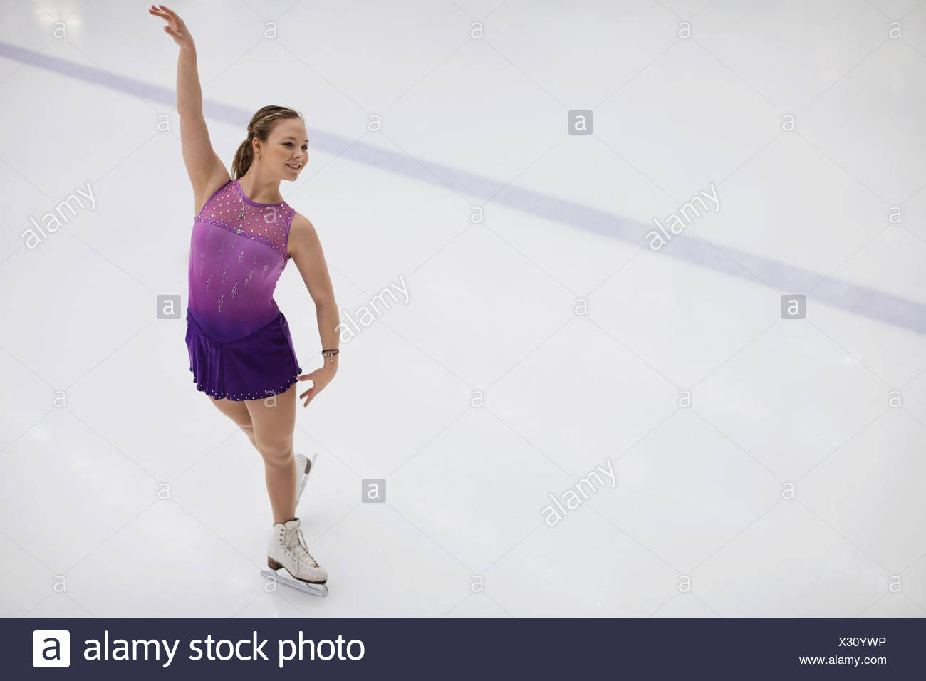 Figura femenina skater realizando la rutina en una pista de patinaje Foto de stock