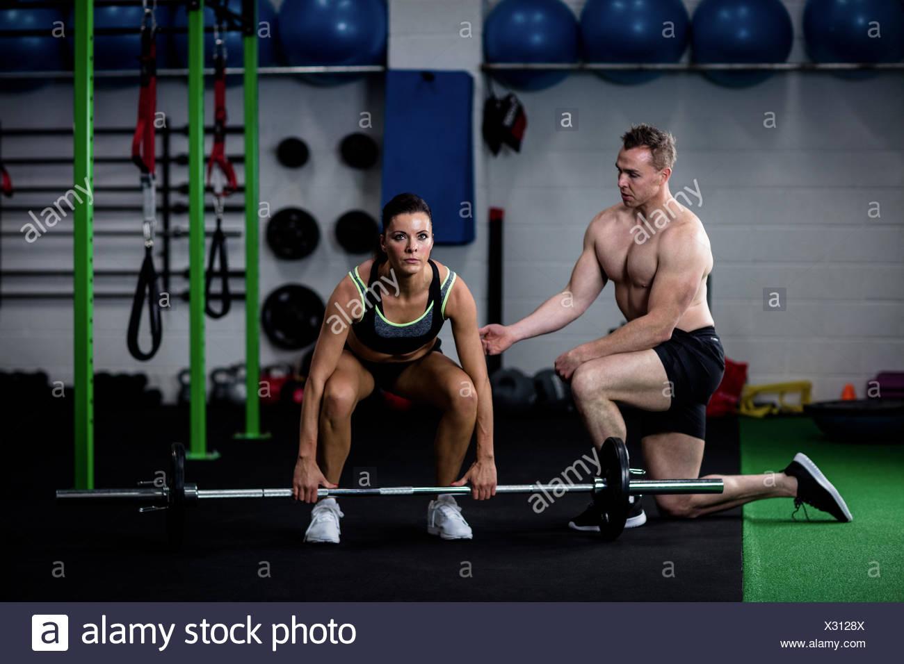 Formador instruir a una mujer mientras levanta barbell Imagen De Stock