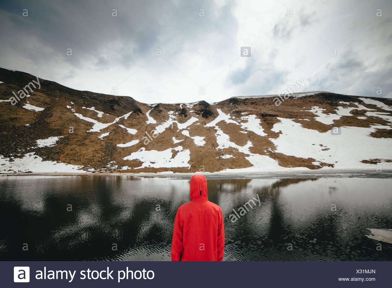 Vista posterior del joven mirando al lago de montaña Imagen De Stock