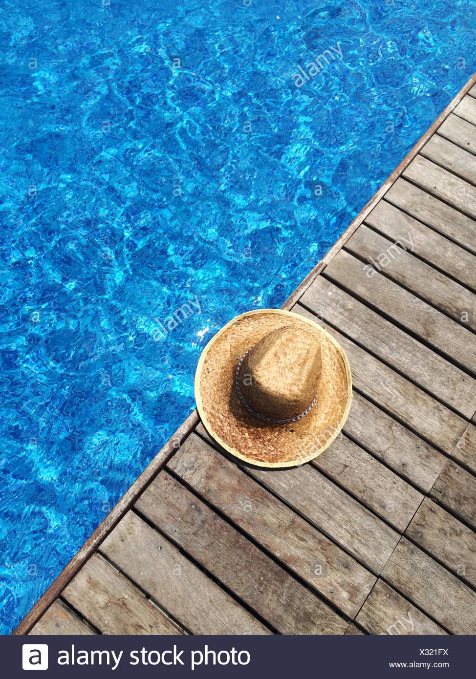 Paja sombrero para el sol por la piscina Foto de stock