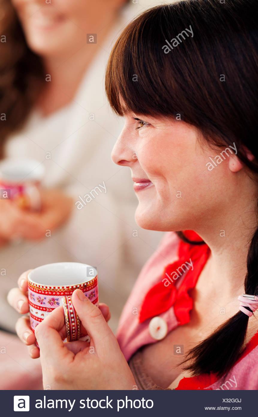 Vista lateral de la mujer bebiendo vino caliente en navidad Imagen De Stock