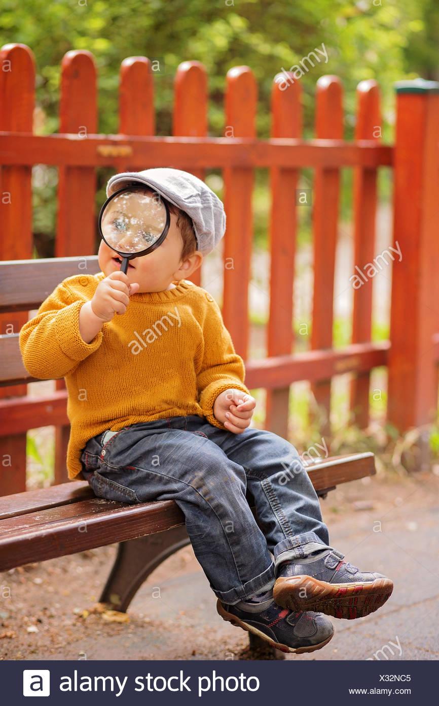 Muchacho sentado en un banco sosteniendo una lupa Foto de stock