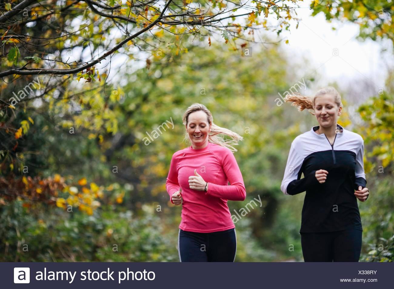 Adolescente y la mujer ejecutando en estacionamiento Imagen De Stock