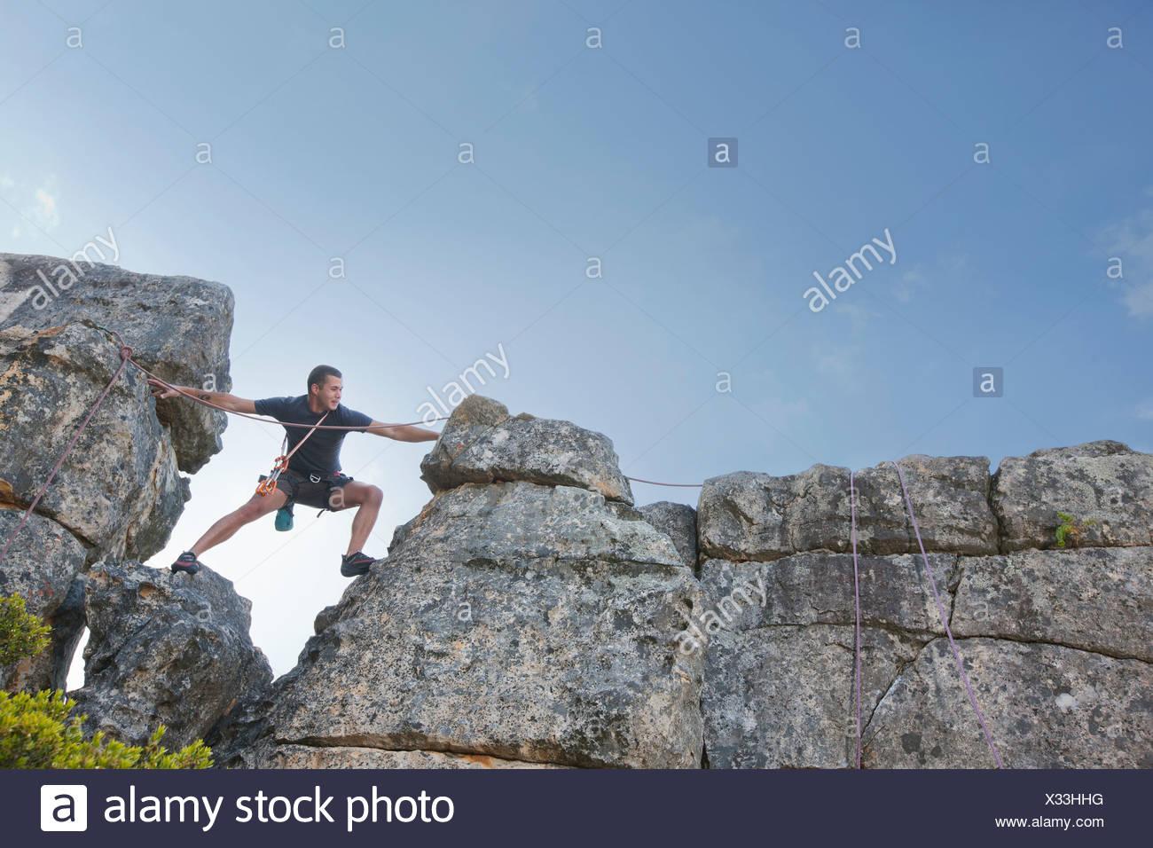 Joven stepping y llegar a escalar en roca Foto de stock