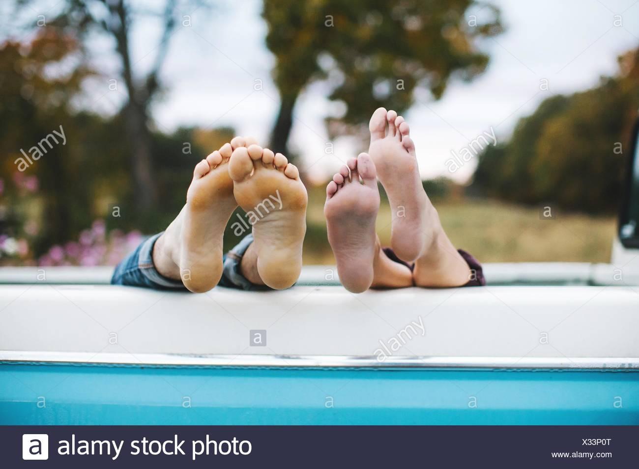 Pareja joven tumbado en la parte trasera de la carretilla, los pies descalzos en el borde de la carretilla, se centran en los pies Imagen De Stock