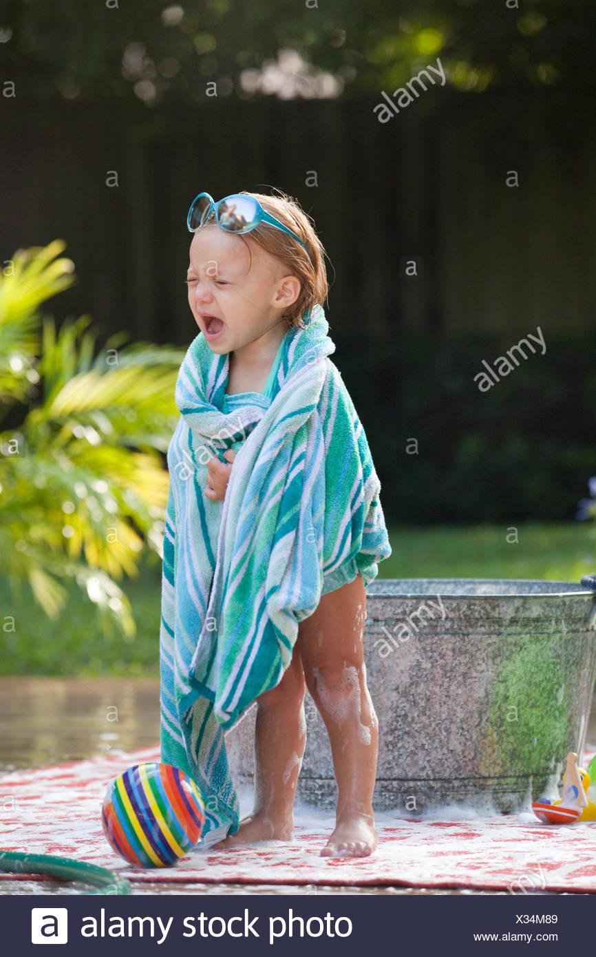 Niño envuelto en una toalla femenina llorando junto al baño de burbujas en el jardín Imagen De Stock