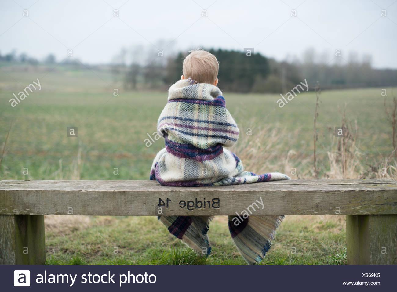 Vista trasera de un muchacho sentado en un banco, envuelto en una cobija caliente Imagen De Stock