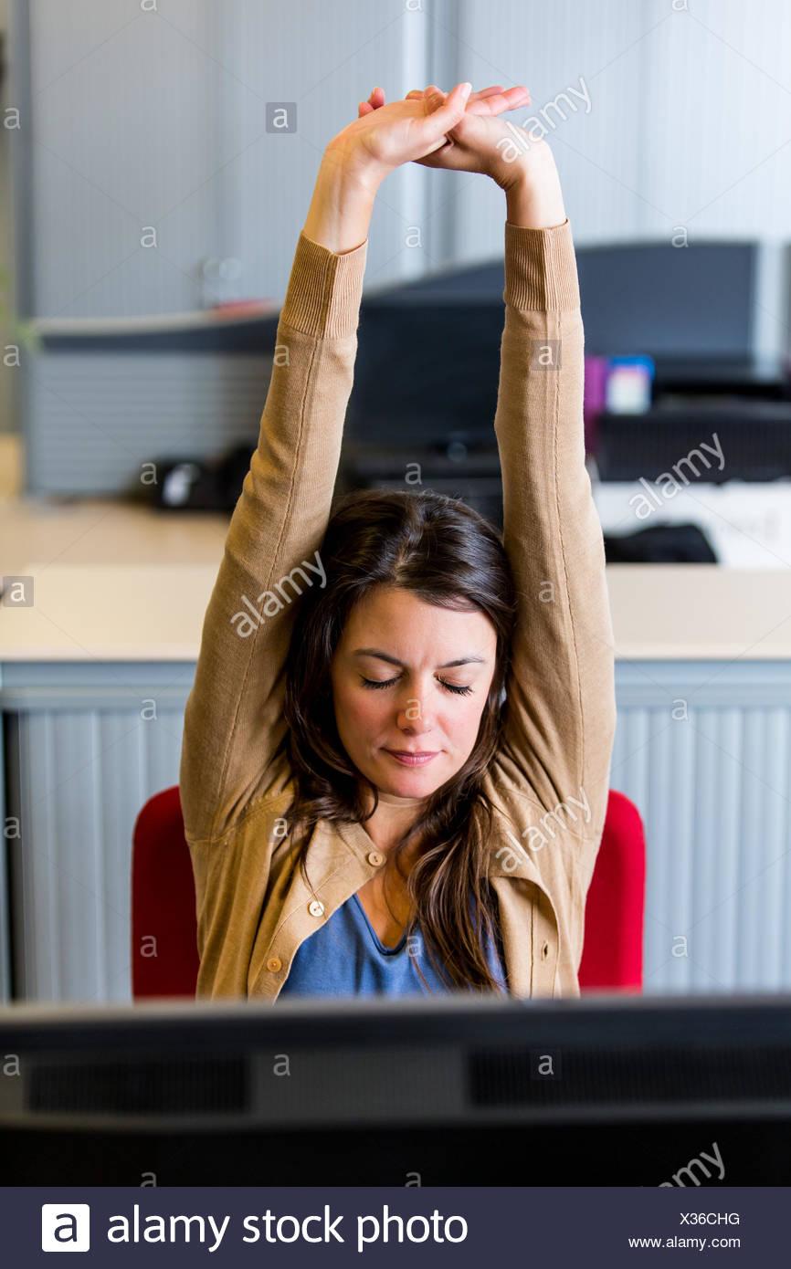 Oficina mujer estirando los brazos en el trabajo. Imagen De Stock