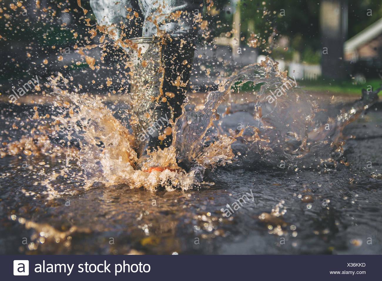 Cerca de las piernas del niño chapotear en un charco de agua Imagen De Stock