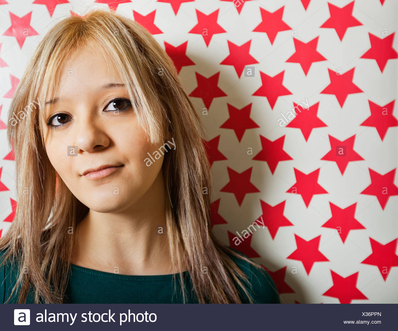 Cerca de la hermosa joven gainst formas de estrella roja papel tapiz Foto de stock