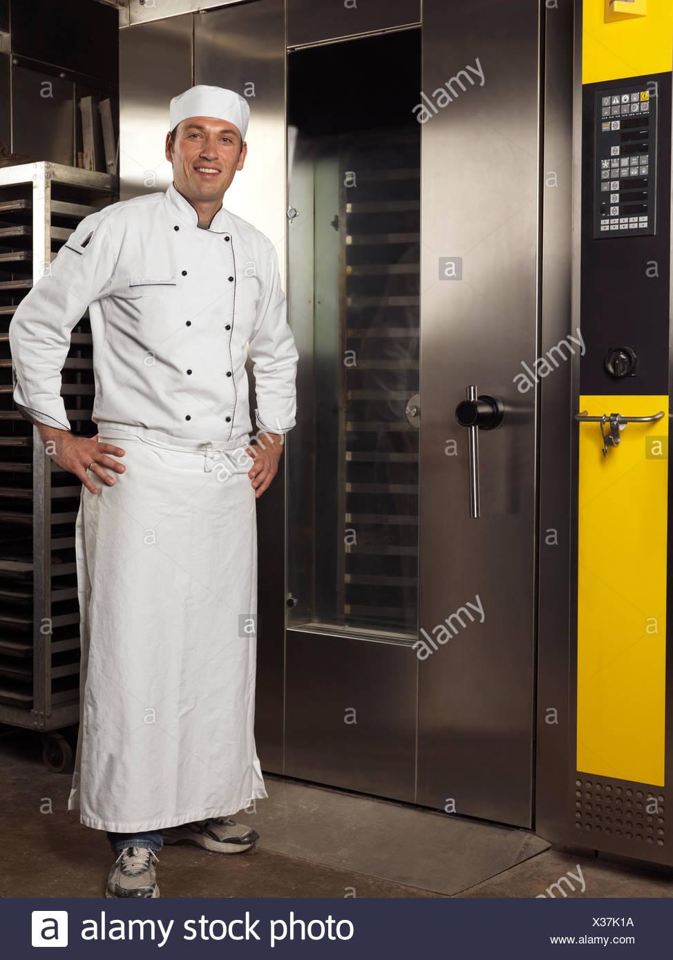 Baker sonriente frente a un horno de panadería comercial Imagen De Stock