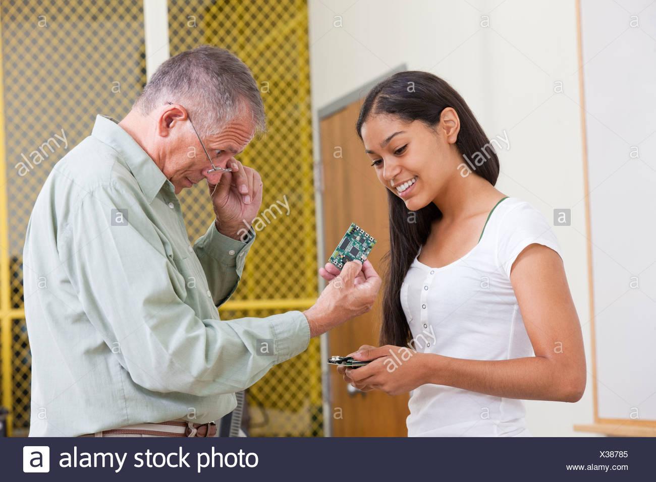 Profesor de Ingeniería mostrando las placas de circuito para un estudiante Imagen De Stock