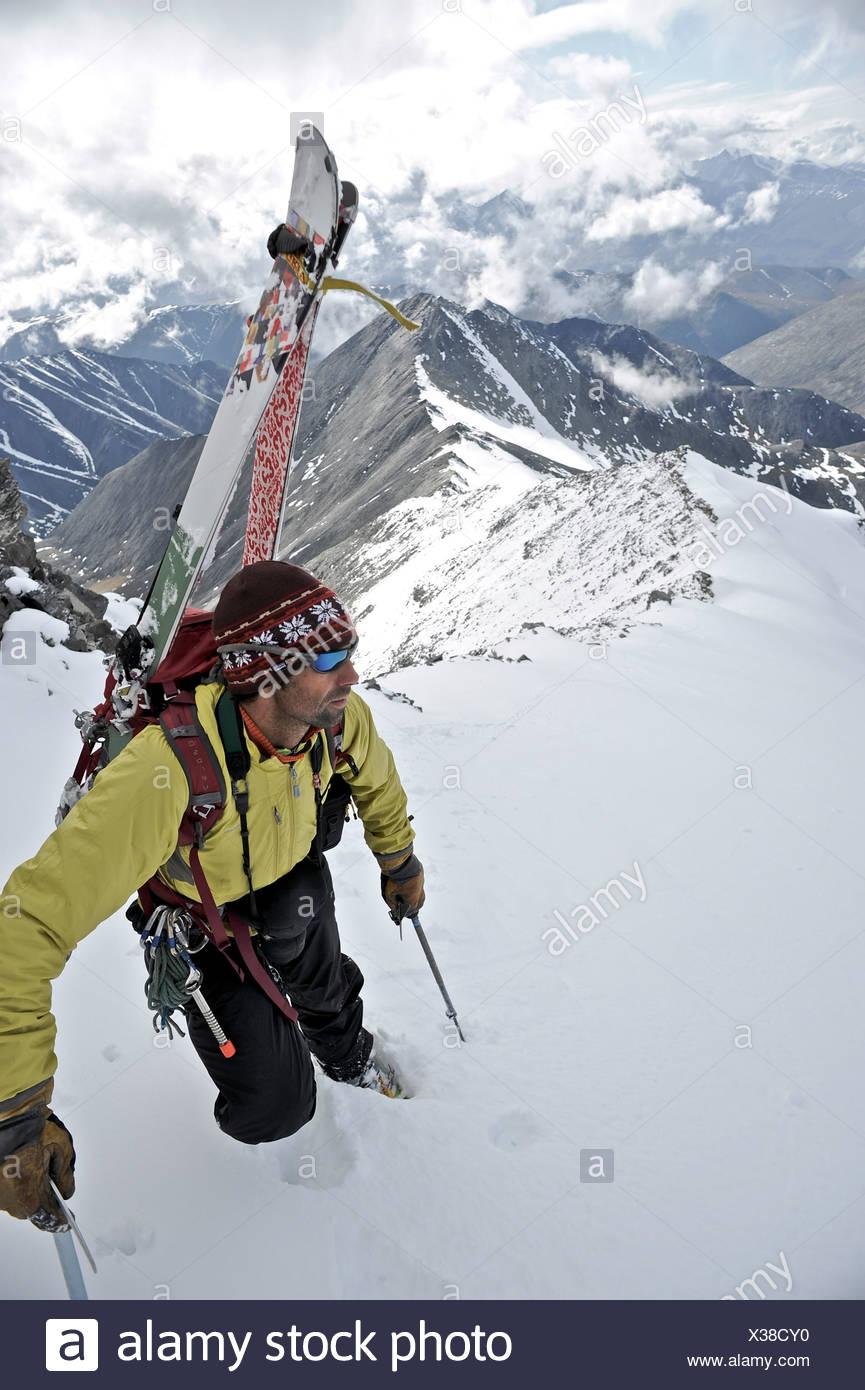 Backpacker mira sobre la escena siguiente como él sube la cresta oeste de Mt. Chamberlin en la sierra Brooks, ANWR, Arctic Alaska Foto de stock