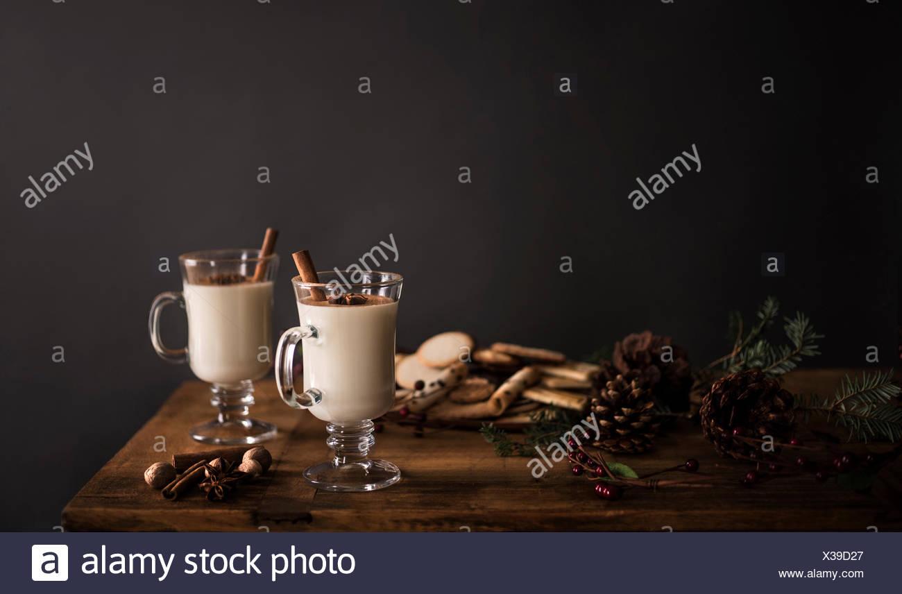 2 vasos de ponche de huevo en una mesa de madera con adornos de fiestas contra una pared gris sólido. Imagen De Stock