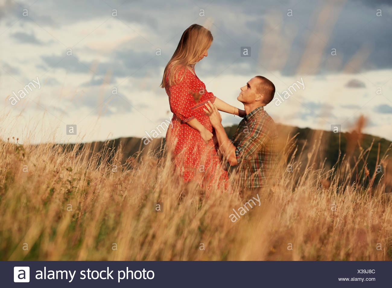 A mediados adulto hombre arrodillado con la mano en el estómago de esposa embarazada en el campo Imagen De Stock