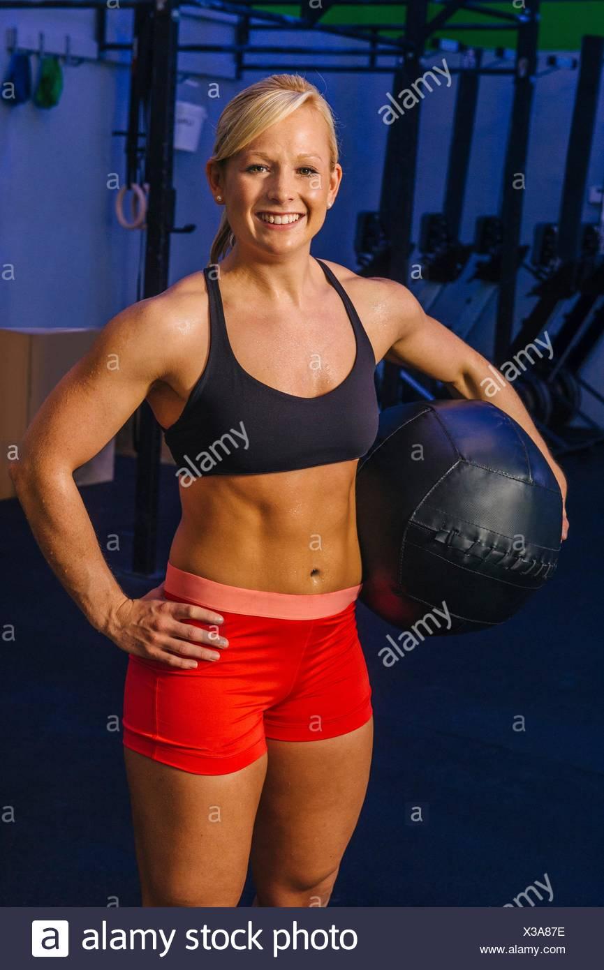 Retrato de mujer joven formación en gimnasio con balón medicinal Imagen De Stock