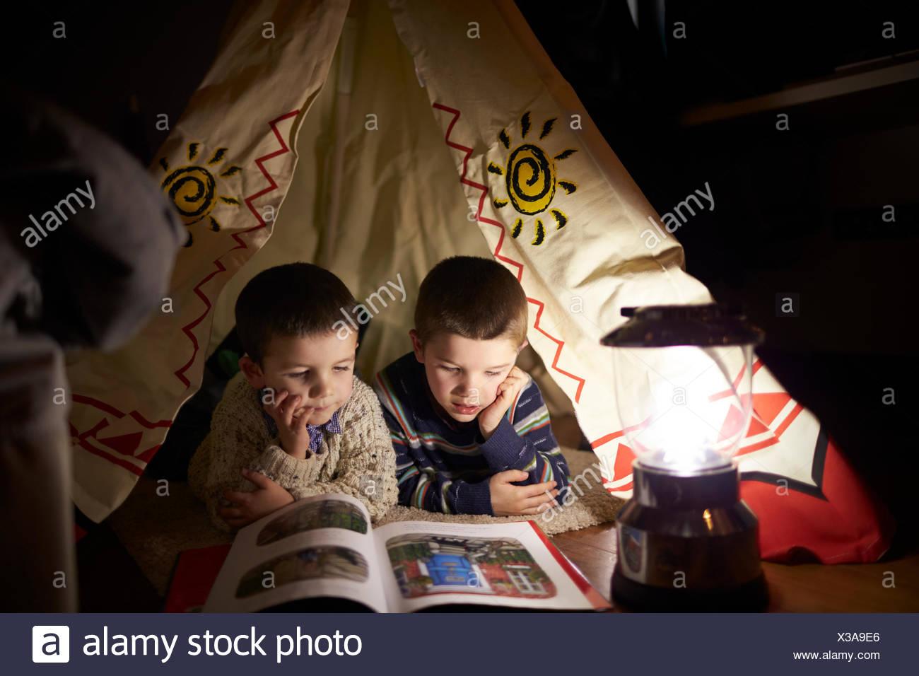 Dos chicos Leer adentro tienda de campaña establecido en interiores Imagen De Stock