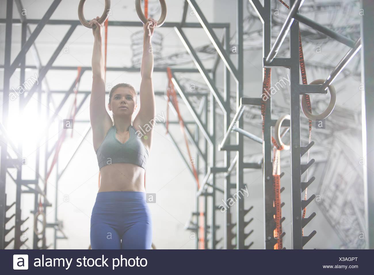 Seguros de la mujer ejerce con anillos de gimnasia en el gimnasio crossfit Foto de stock