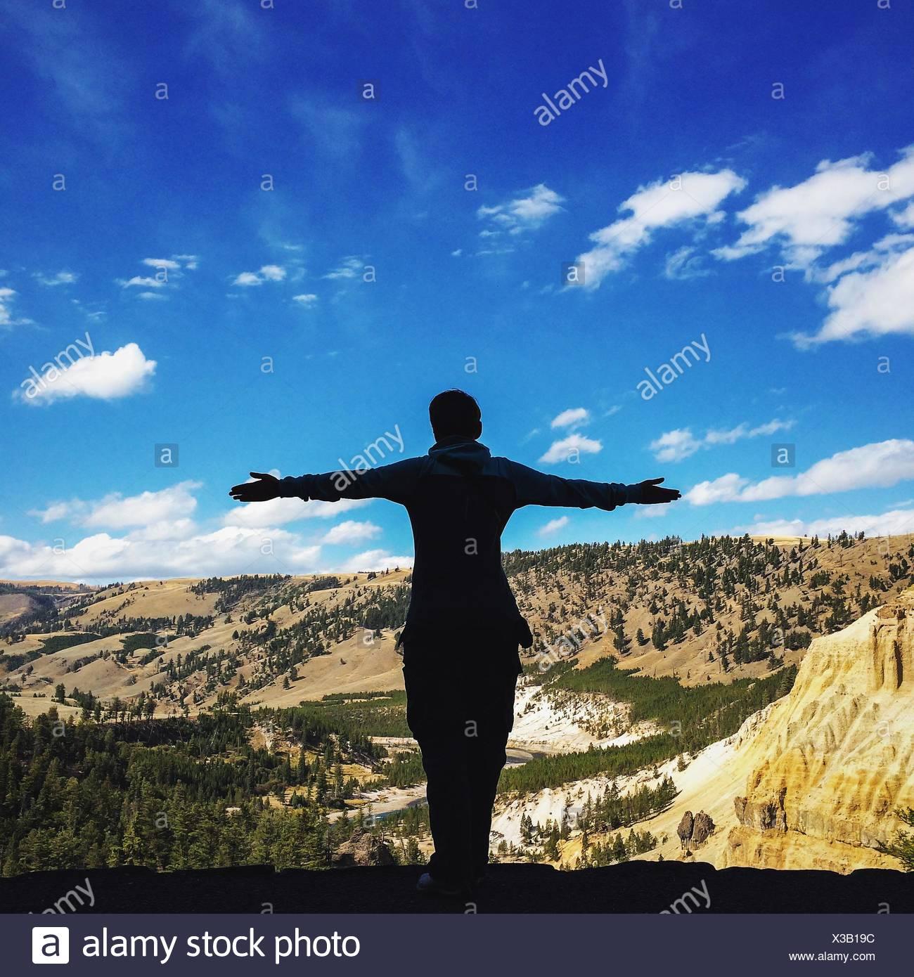 Vista trasera del hombre de pie con los brazos extendidos por las montañas contra el cielo Foto de stock