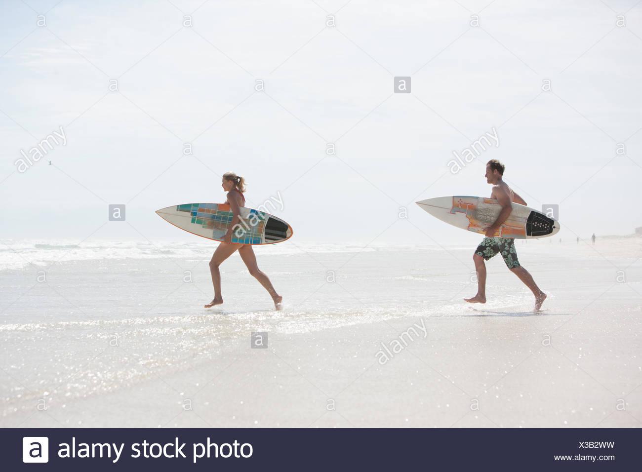 Pareja con tablas de surf en la playa corriendo Imagen De Stock