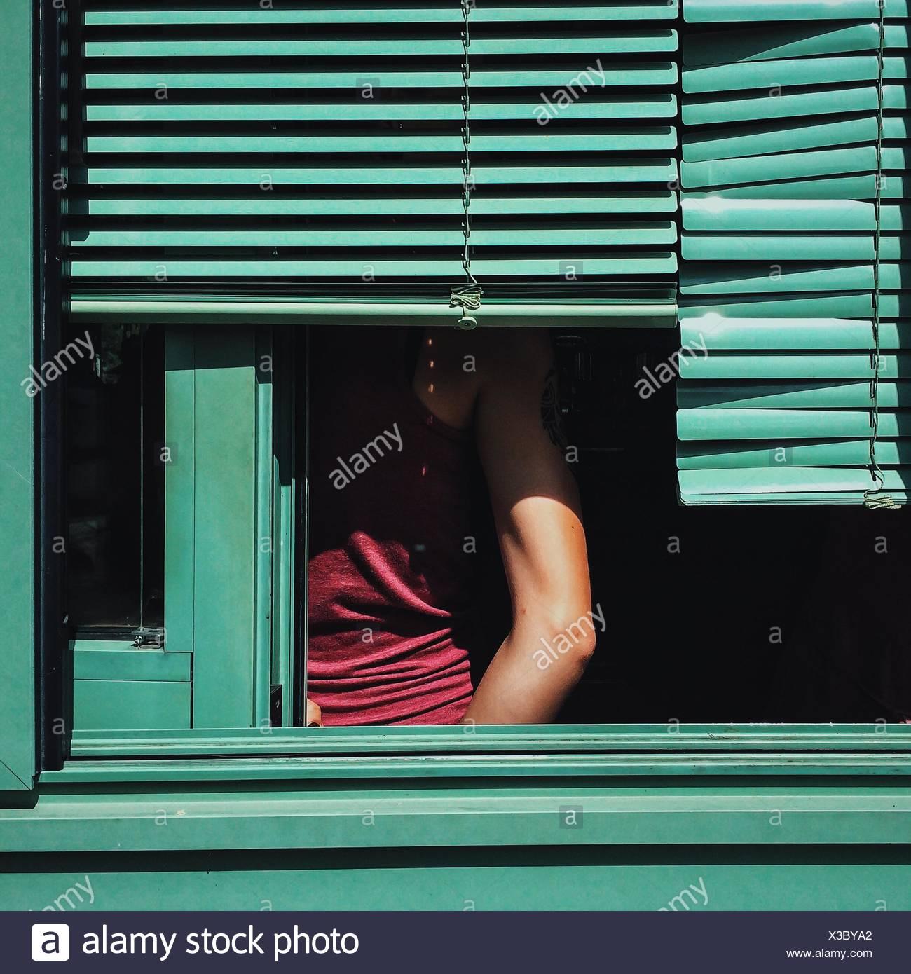 Parte media del hombre visto a través de la ventana Imagen De Stock