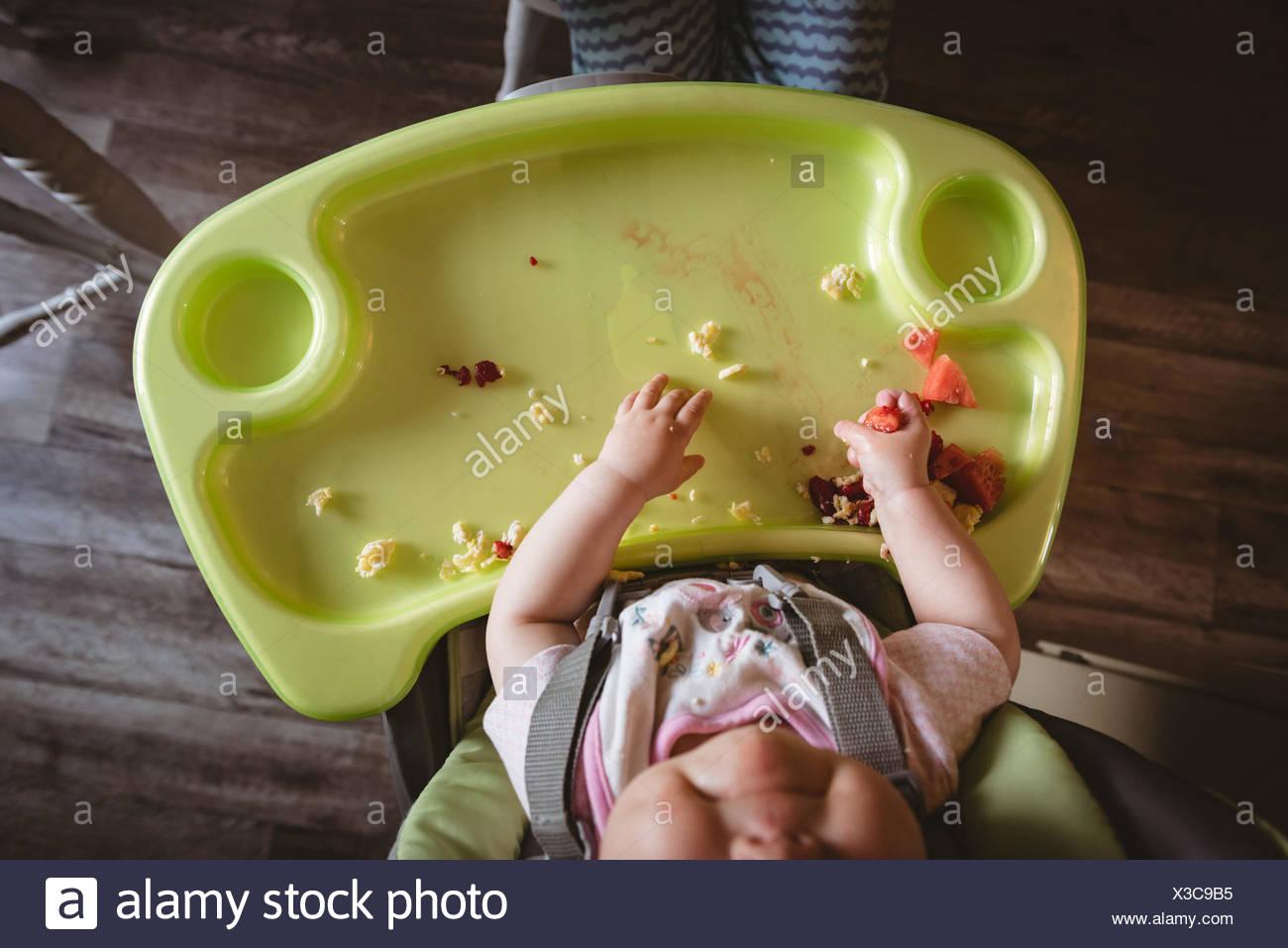 Sobrecarga de bebé sentado en la silla alta Imagen De Stock