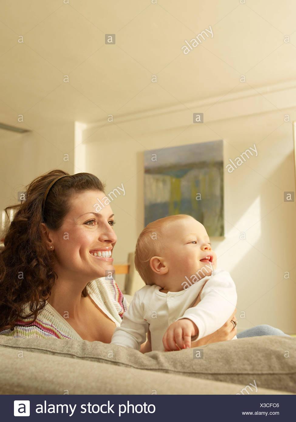 Madre sosteniendo bebé, vista lateral Foto de stock