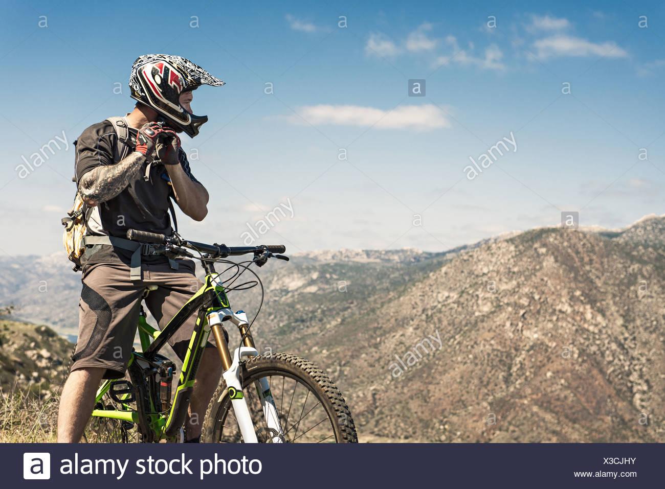 Ciclista de montaña cuesta abajo poniendo en el casco Foto de stock