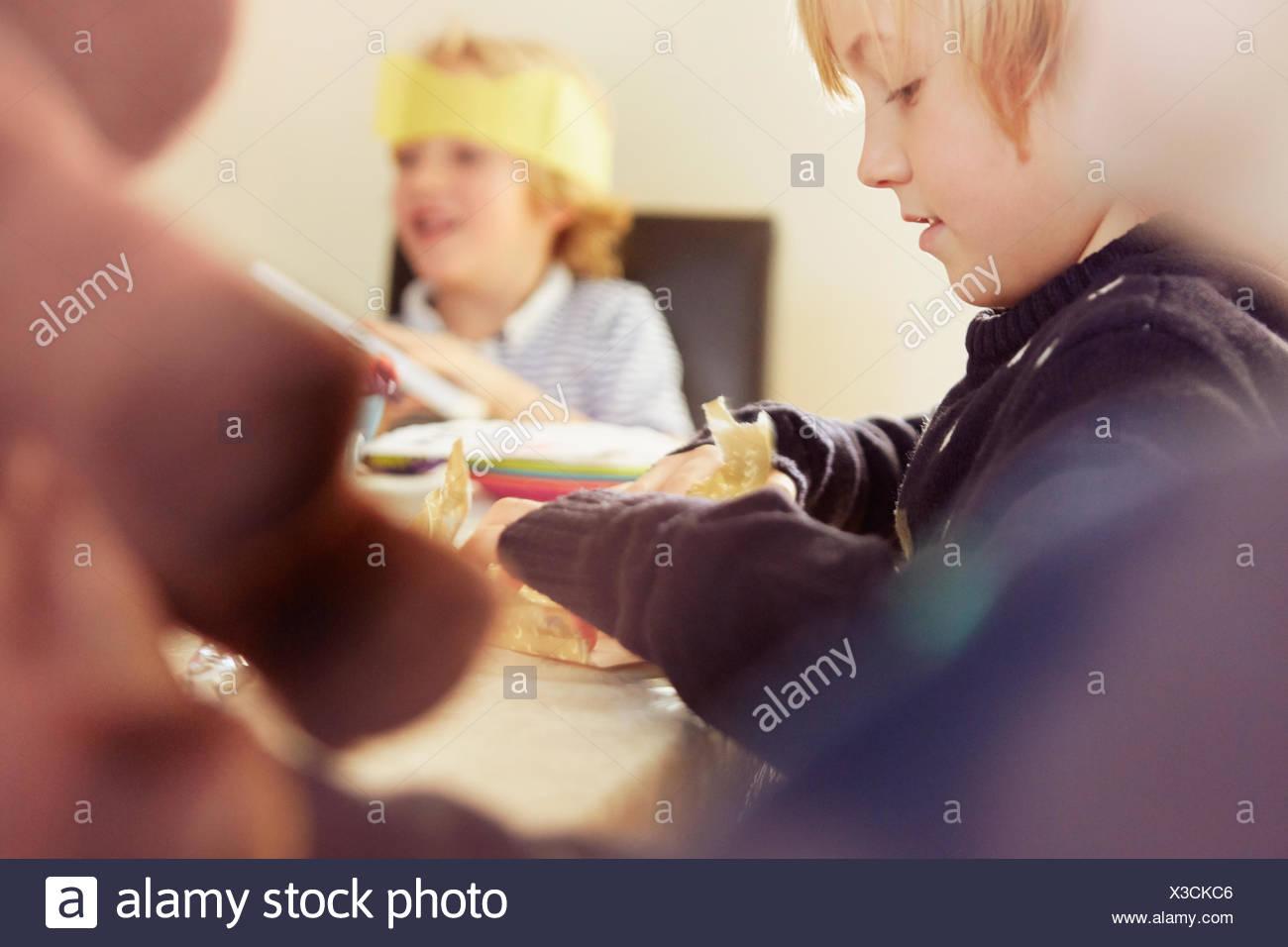 Niño abriendo regalo de Navidad en la mesa Imagen De Stock