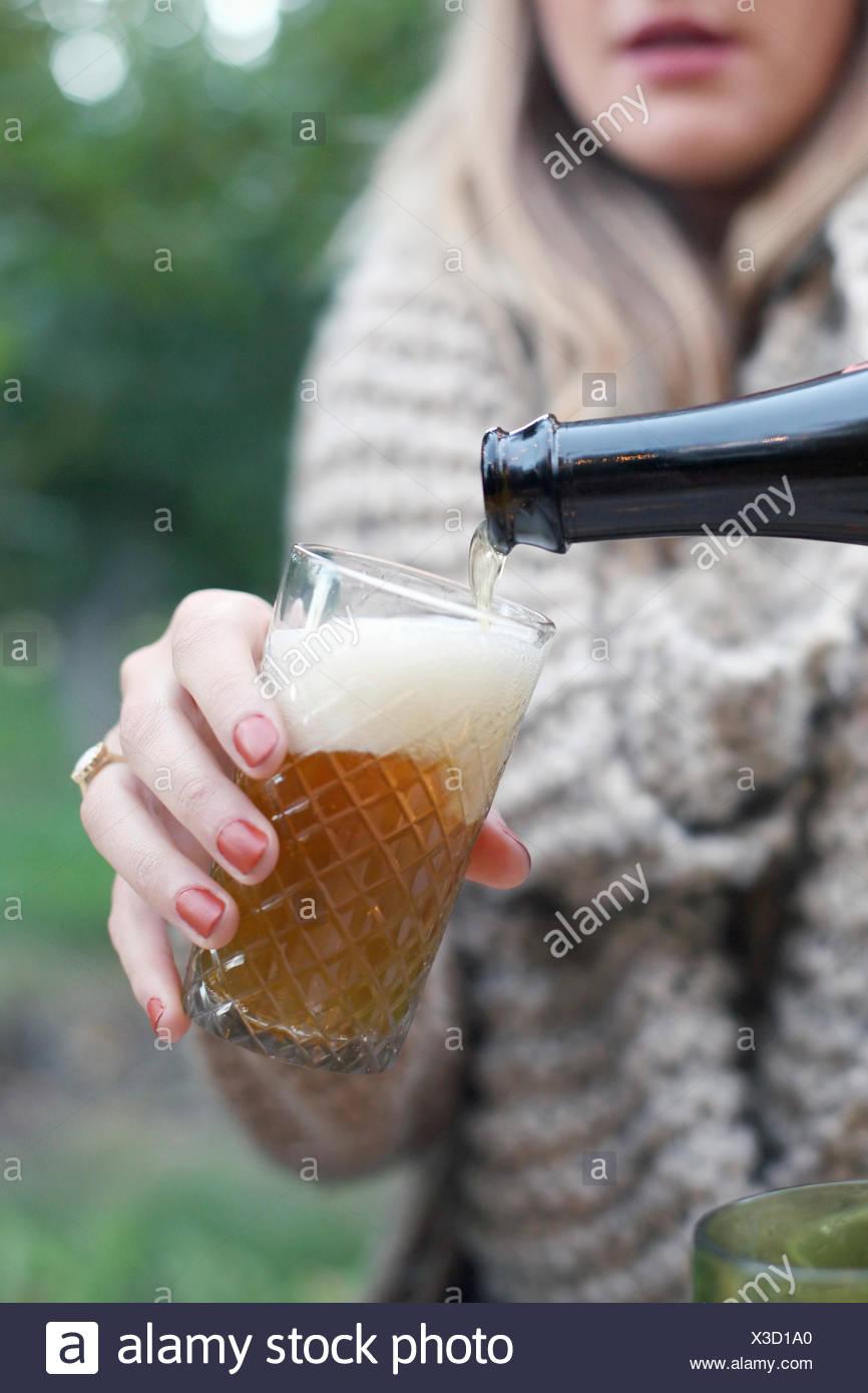 Huerto de Manzanas. Mujer vertiendo un vaso de sidra. Imagen De Stock