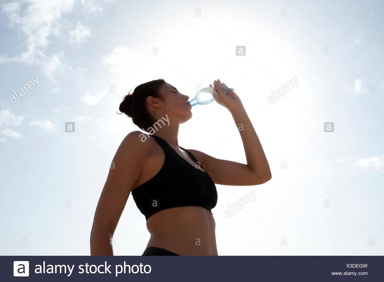 Vista de ángulo bajo un cielo azul y mitad mujer adulta beber agua embotellada Imagen De Stock