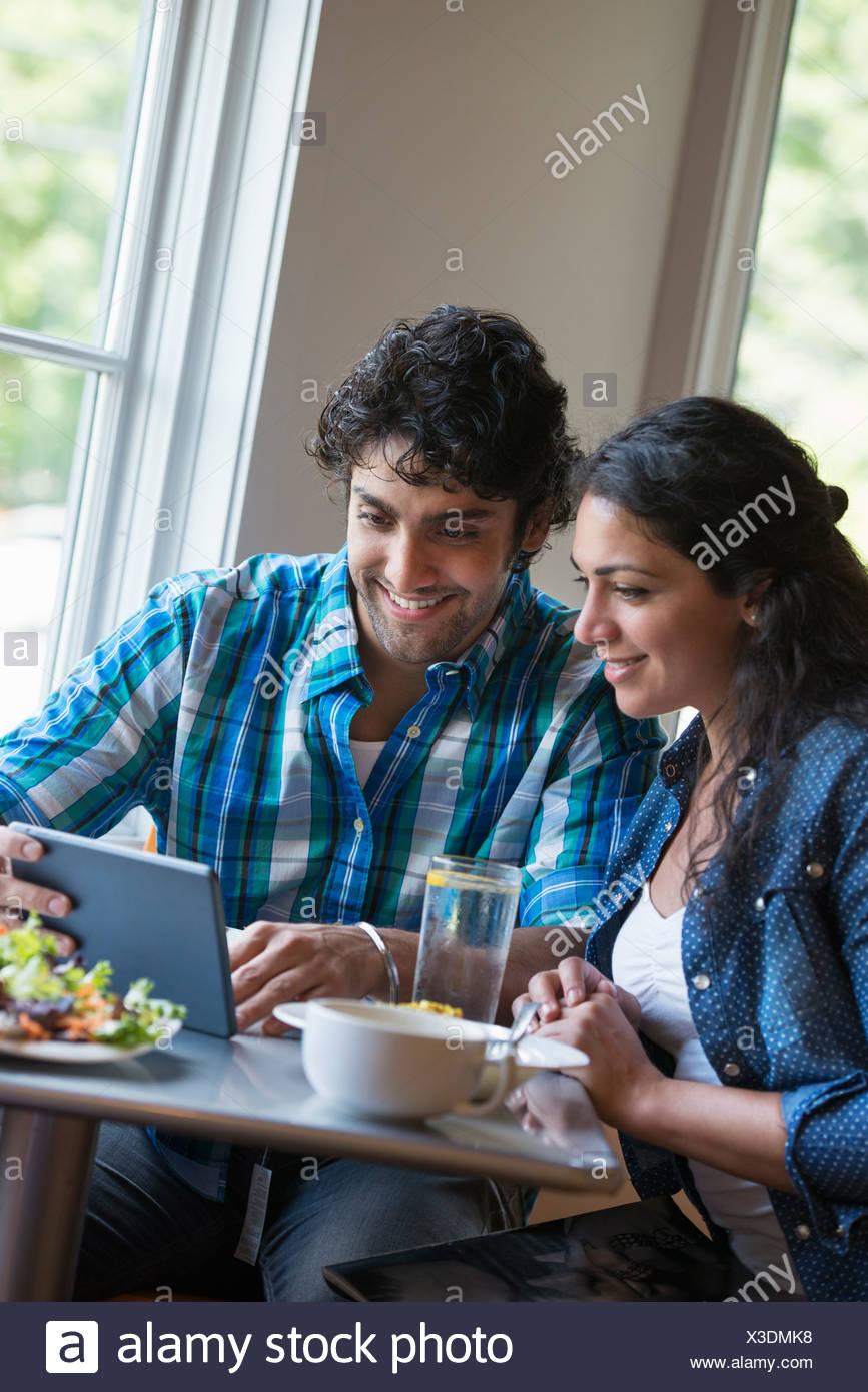 Una pareja sentada mirando una tableta digital. Imagen De Stock