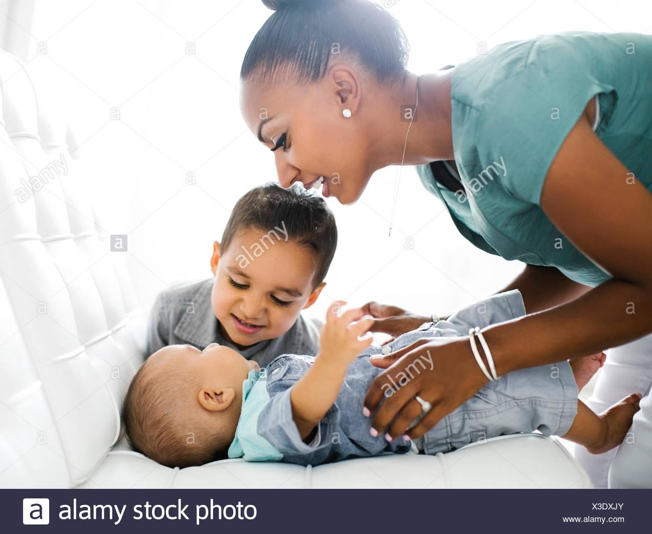 Madre de dos hijos (2-5 meses, 2-3) en el sofá Imagen De Stock