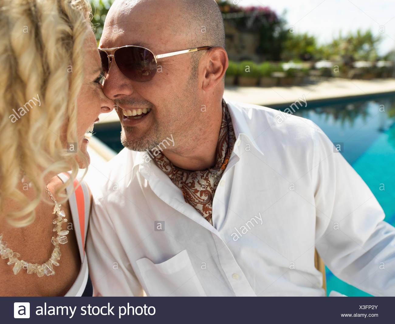 Un bien construido joven toca la punta de la nariz de una mujer bonita por su punta por el lado de la piscina en San Diego. Foto de stock