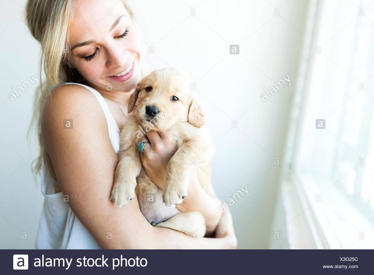 Mujer sosteniendo cachorro golden retriever Imagen De Stock