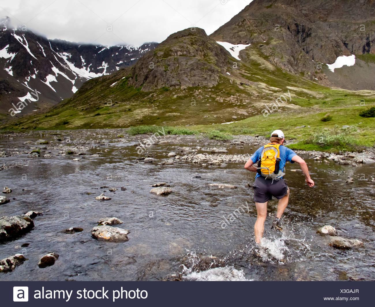 Trail Runner salpica a través de la Bifurcación Medio Campbell Creek mientras ejecuta el Monte Elliot a Wolverine Pico a punto oxidado, Alaska Imagen De Stock