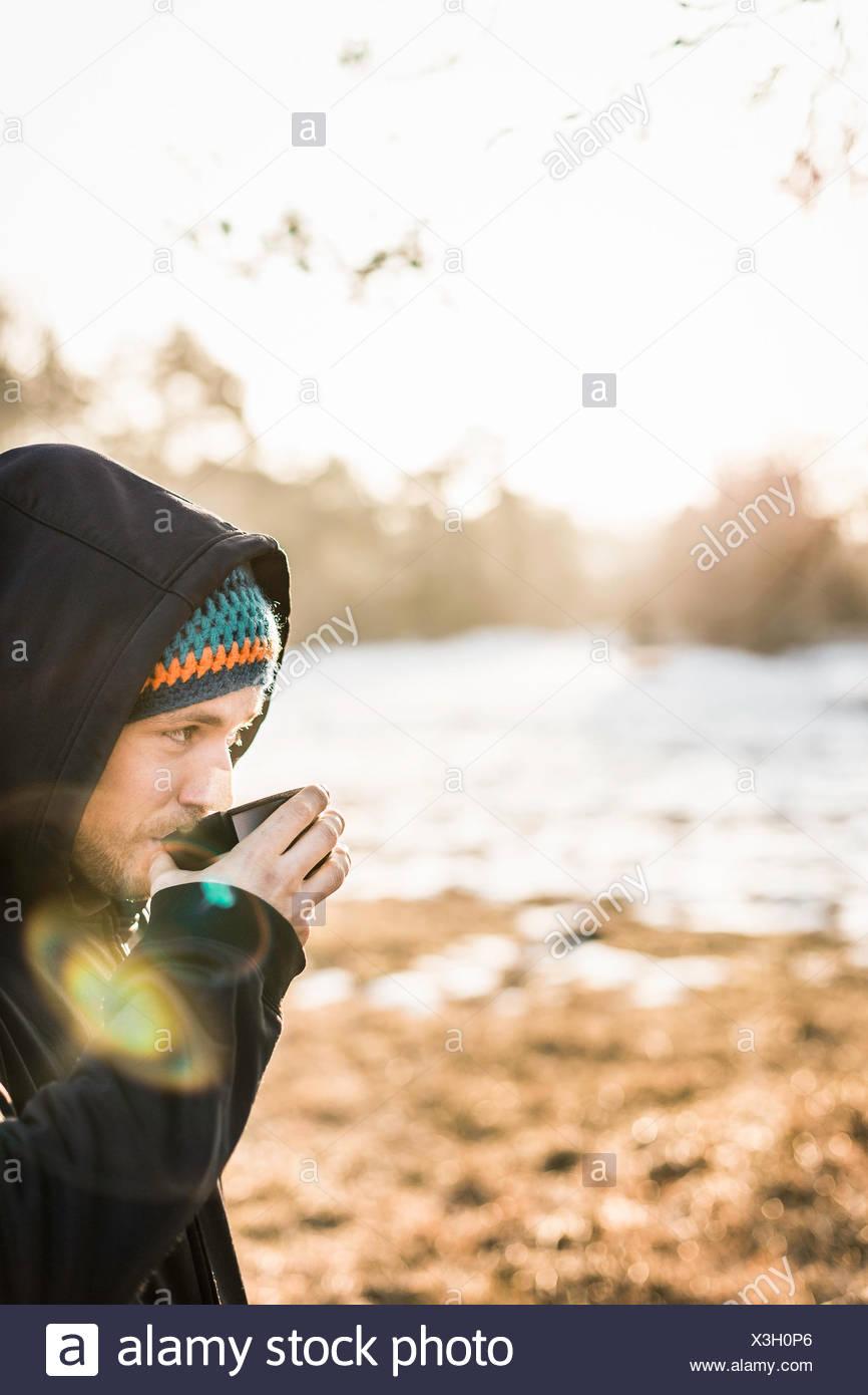 Retrato de joven bebiendo café en lakeside Imagen De Stock