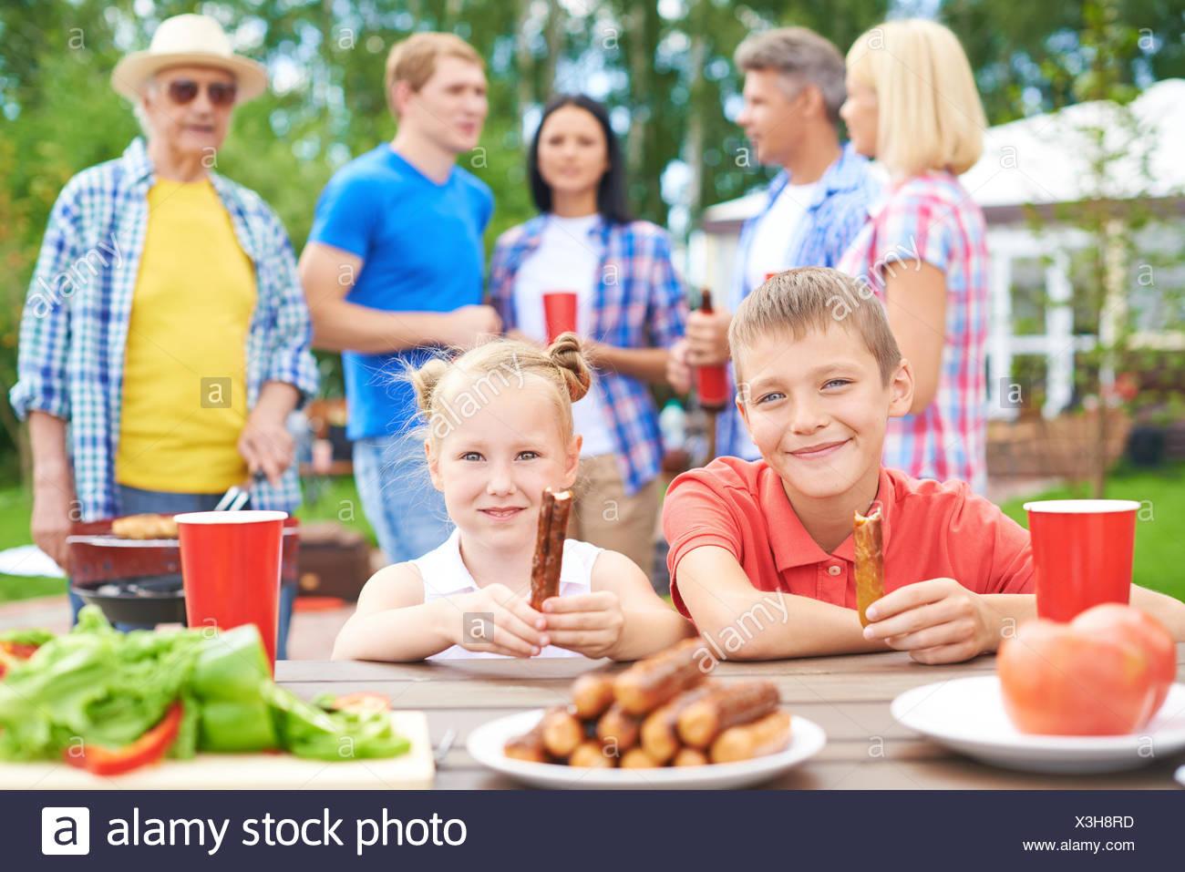 Los Niños Que Comen Salchichas Durante Su Reunión Familiar Foto