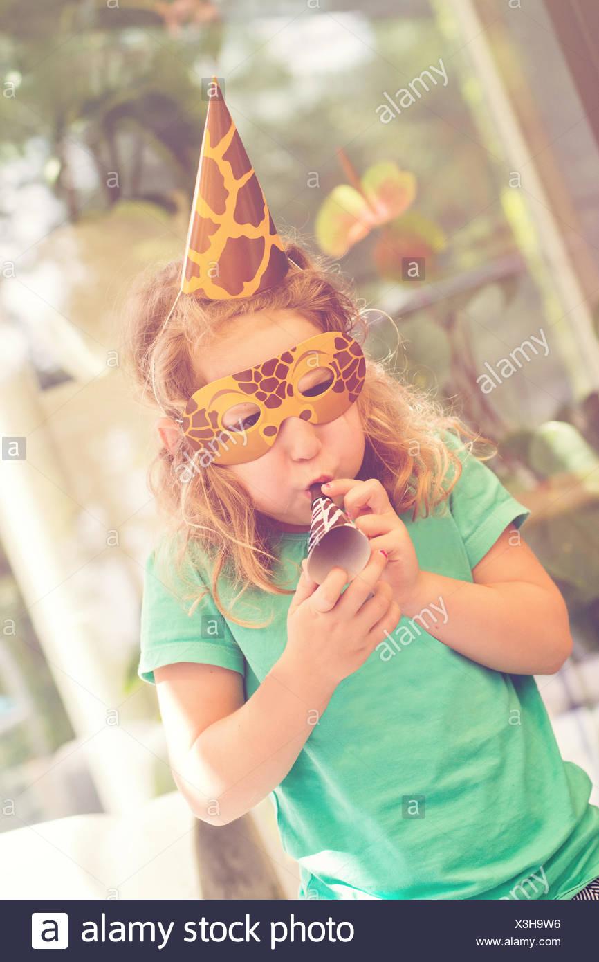Chica en una máscara en una fiesta de cumpleaños con un ventilador del partido Imagen De Stock