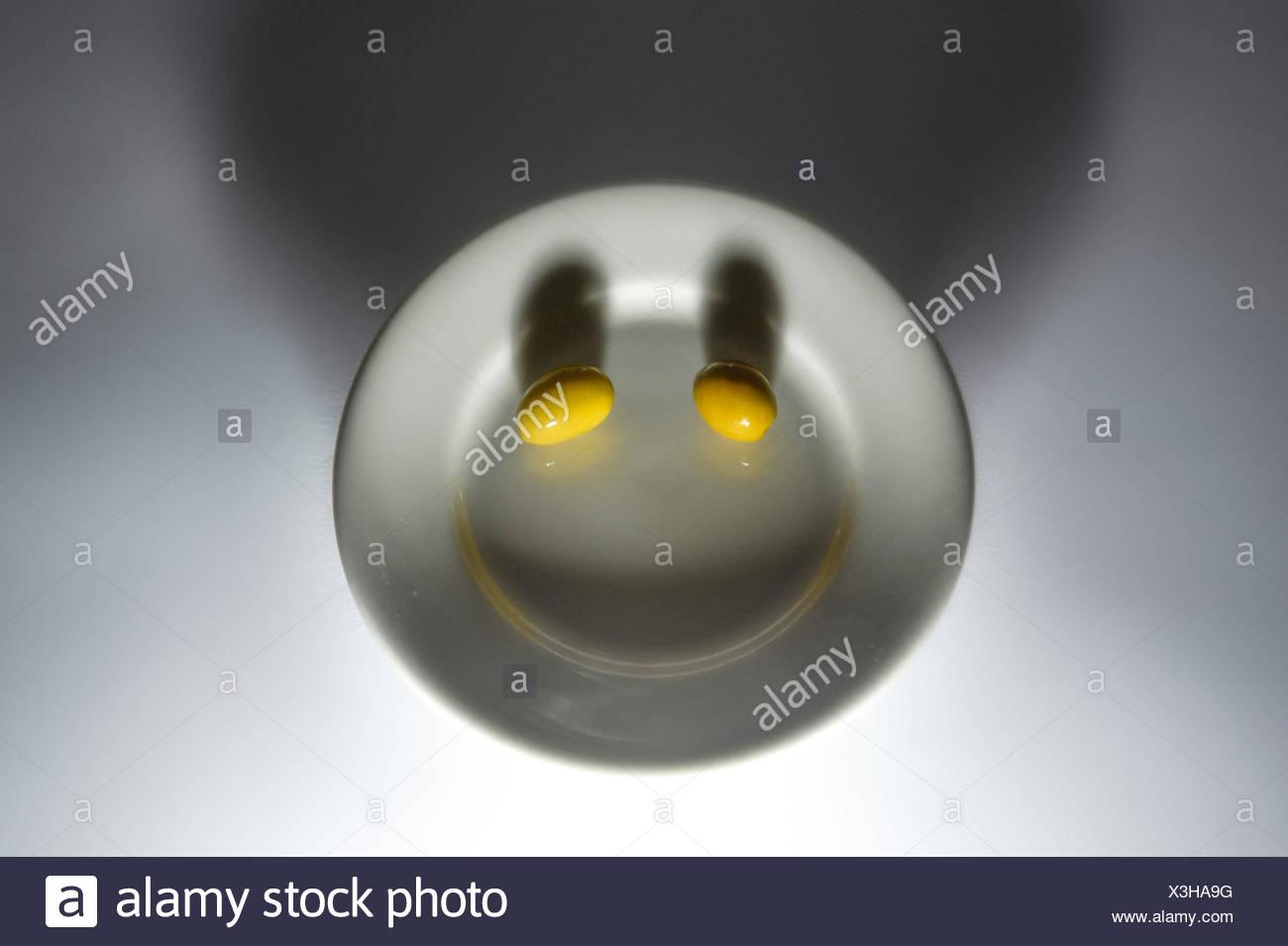 Dos aceitunas en una placa haciendo cara sonriente Foto de stock